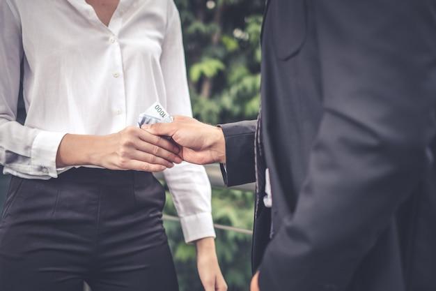 Hommes d'affaires faisant la poignée de main avec de l'argent dans les concepts de corruption