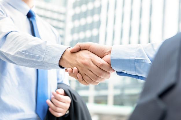 Hommes d'affaires faisant la poignée de main à l'extérieur en face d'immeubles de bureaux dans la ville