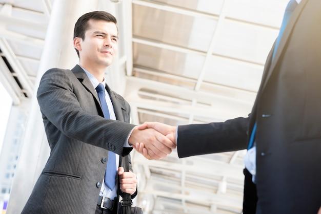 Hommes d'affaires faisant une poignée de main sur une passerelle couverte en plein air