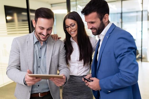 Hommes d'affaires et femme d'affaires utilisant une tablette numérique au bureau
