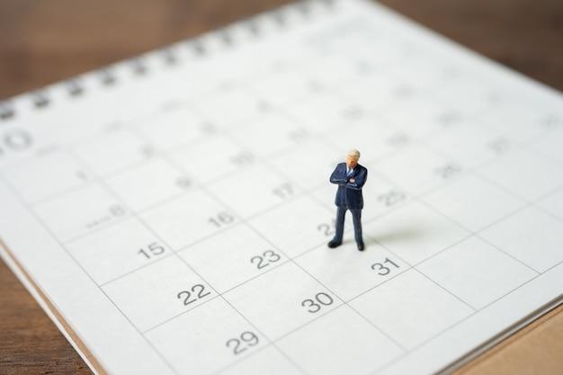 Hommes d'affaires de gens miniatures debout sur un calendrier blanc