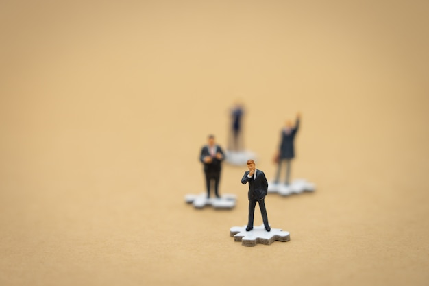 Hommes d'affaires de gens miniatures sur puzzle blanc