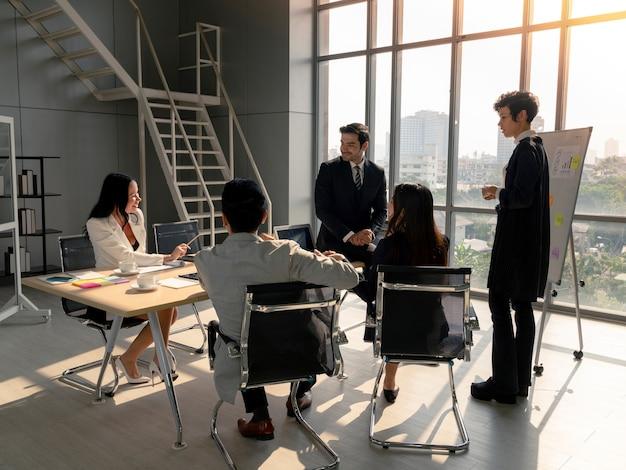 Des hommes d'affaires heureux de la diversité réfléchissent et discutent de l'analyse de la stratégie de planification à partir du rapport de document financier lors d'une réunion d'affaires au bureau, du travail d'équipe, de l'analyse commerciale et du concept de stratégie