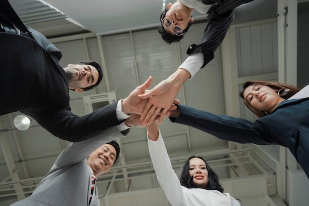 Des hommes d'affaires heureux empilent leurs mains en cercle, montrent ensemble, unissent le concept, une équipe réussie