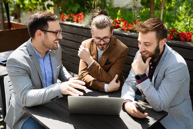 Hommes d'affaires heureux et joyeux utilisant un ordinateur portable lors de la réunion en plein air