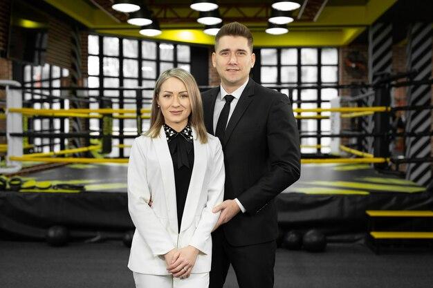 Les hommes d'affaires hommes et femmes en costume posent dans le contexte d'un ring de boxe.