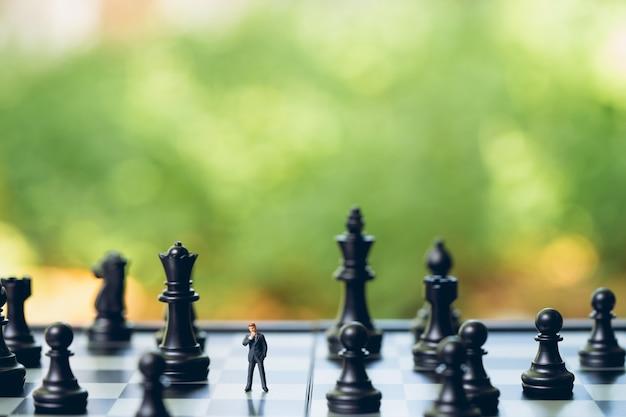 Hommes d'affaires d'hommes miniatures debout analyse d'échecs communiquer