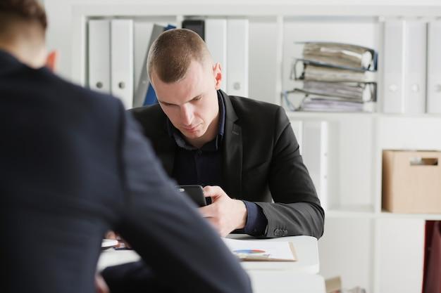 Hommes d'affaires lisant la revue financière au tablet pc au bureau.