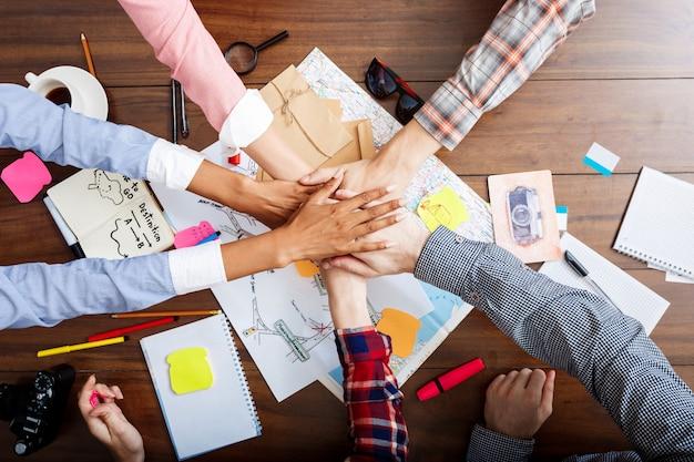 Hommes d'affaires mains sur table en bois avec documents et projets