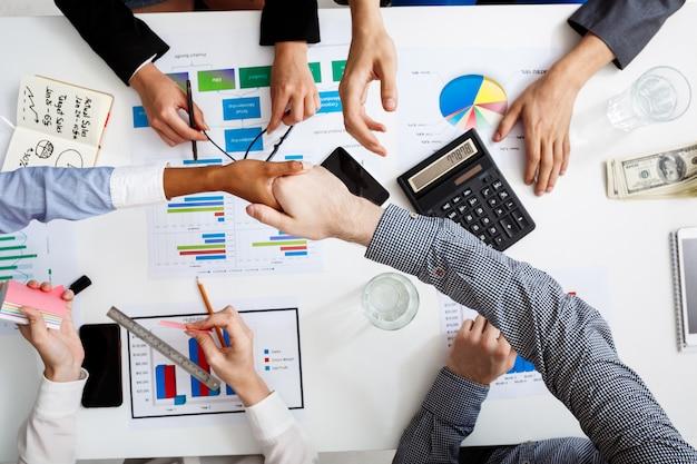 Hommes d'affaires mains sur tableau blanc avec des documents et des projets