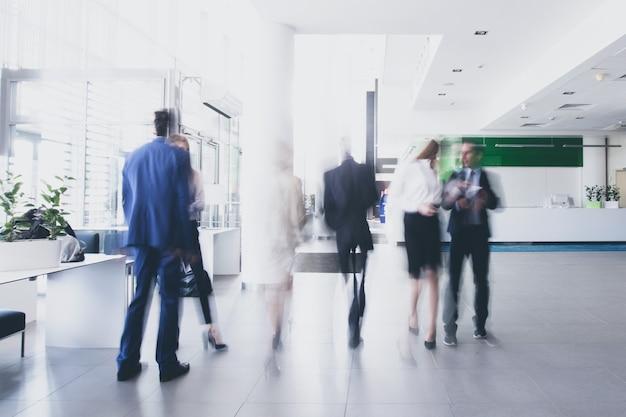 Hommes d'affaires marchant dans le couloir d'un centre d'affaires, flou de mouvement prononcé