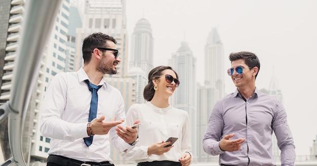 Les hommes d'affaires de la marina de dubaï se rendent à leur bureau et parlent de nouvelles idées et de nouveaux mouvements marketing.
