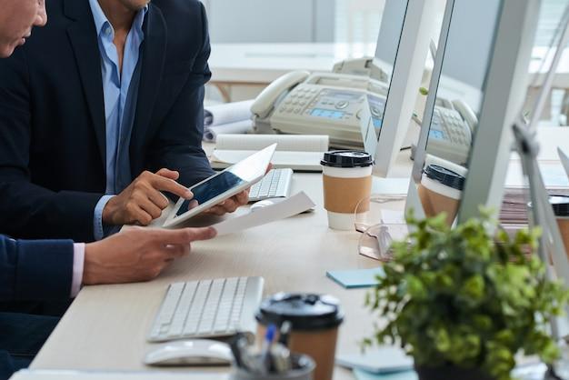Hommes d'affaires méconnaissables assis au bureau et regardant ensemble la tablette et le document