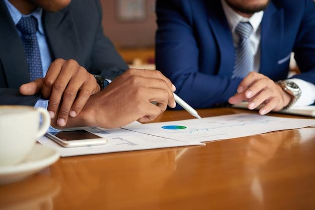 Hommes d'affaires méconnaissables assis à une table lors d'une réunion et analysant des graphiques