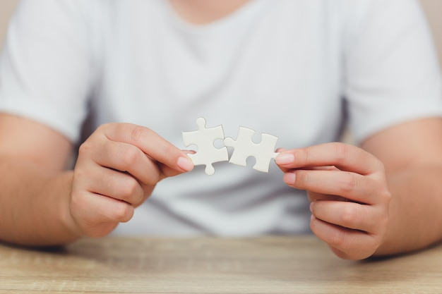 Les hommes d'affaires mettent la dernière pièce du puzzle, concept de service d'entreprise au succès.
