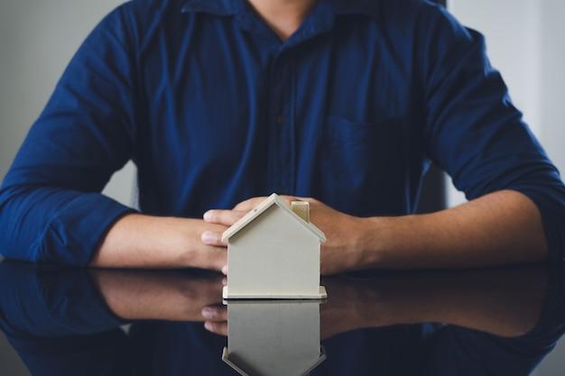 Les hommes d'affaires mettent la maison modèle sur la paume. et les mains