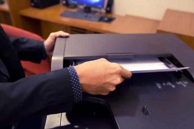 Les hommes d'affaires mettent les papiers aux photocopieurs