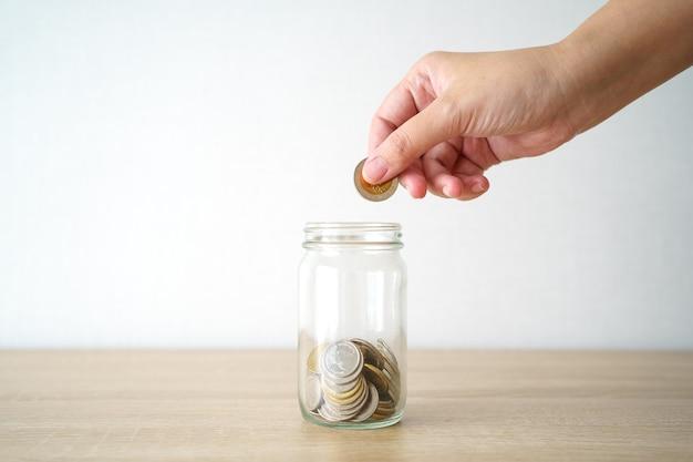 Hommes d'affaires mettez la pièce dans un bocal en verre pour économiser de l'argent, économiser de l'argent sur les investissements,