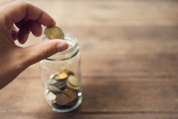 Hommes d'affaires mettez la pièce dans un bocal en verre pour économiser de l'argent