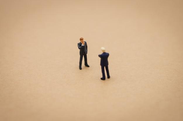 Hommes d'affaires miniatures 2 personnes debout avec le dos négociation en entreprise.