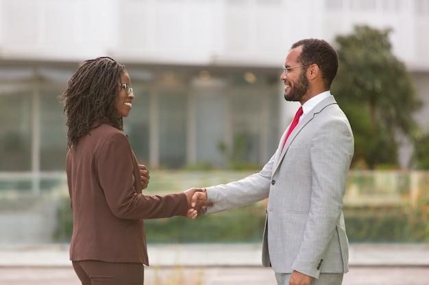 Les hommes d'affaires multiethniques réussis se saluent