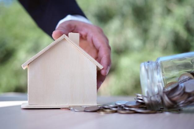 Les hommes d'affaires ont attrapé le modèle de maison et l'argent coulait de la bouteille