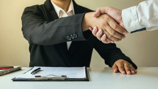 Les hommes d'affaires ont terminé la réunion et la poignée de main de l'heureux homme d'affaires après que le contrat a été conclu pour être un partenaire de travail d'équipe ensemble.