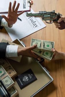 Les hommes d'affaires paient le dollar aux autres parce que forcés et intimidés par les armes