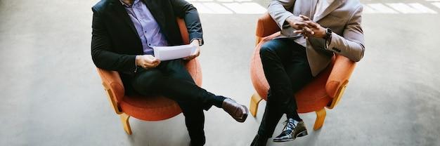Hommes d'affaires parlant et assis sur des chaises bannière sociale