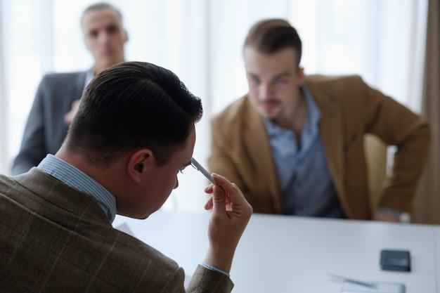 Hommes d'affaires pensifs assis à une réunion du conseil d'administration réfléchissant à un problème ou à une situation.