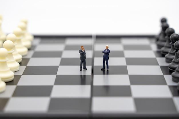 Hommes d'affaires de personnes miniatures debout sur un échiquier avec une pièce d'échecs sur
