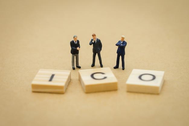 Hommes d'affaires de personnes miniatures debout avec mot de bois ico (initial coin offer)