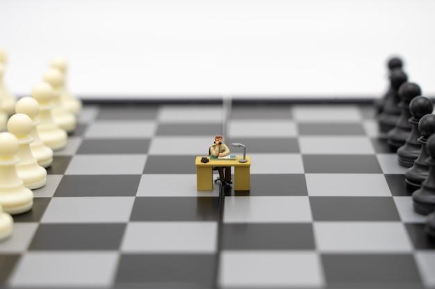 Hommes d'affaires de personnes miniatures sur un échiquier avec une pièce d'échecs