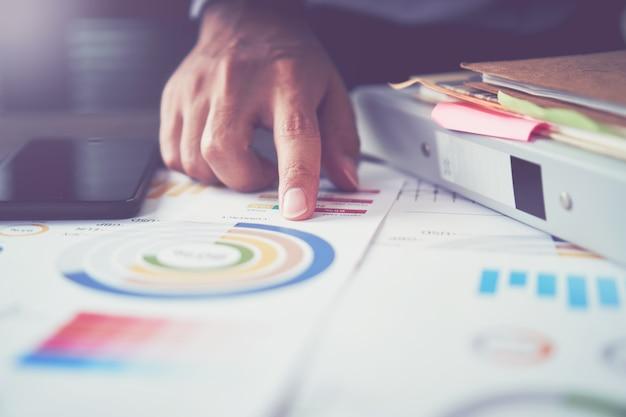 Les hommes d'affaires pointent leur doigt vers les tableaux financiers