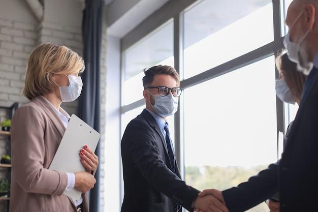 Des hommes d'affaires portant des masques médicaux se serrant la main, terminant une réunion.