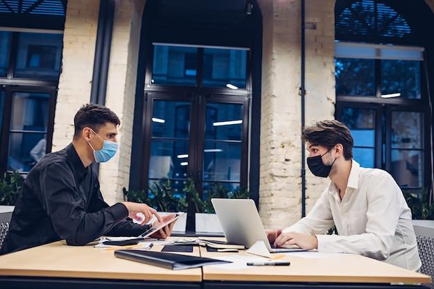 Hommes d'affaires portant des masques médicaux travaillant à table au bureau