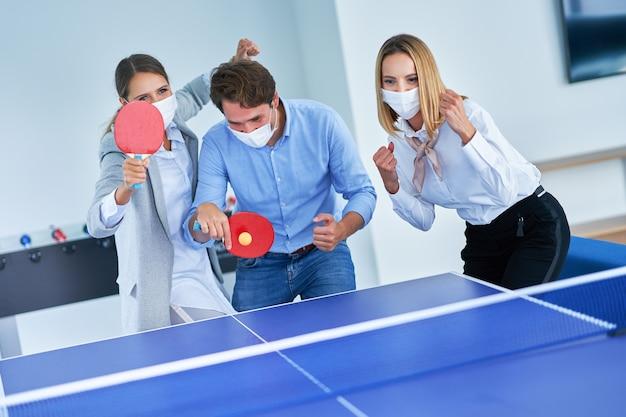 Hommes d'affaires portant des masques de protection jouant au tennis de table dans des bureaux partagés