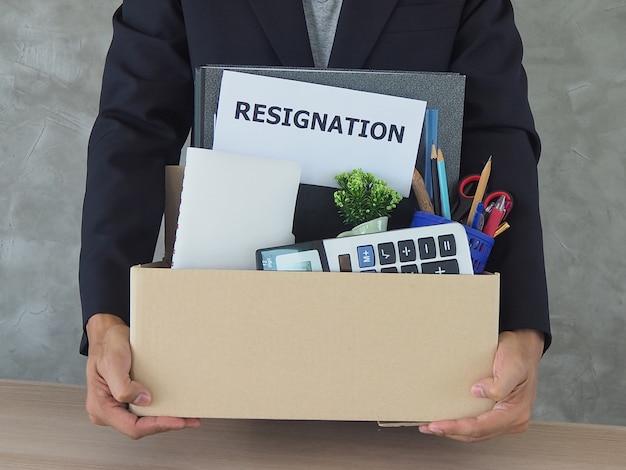 Les hommes d'affaires possèdent des affaires personnelles et des lettres de démission