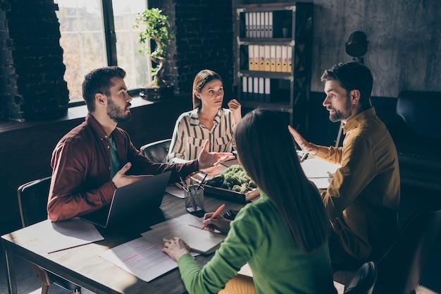 Des hommes d'affaires professionnels qualifiés et expérimentés portant des vêtements de cérémonie décontractés discutant de la croissance financière d'un accord contractuel