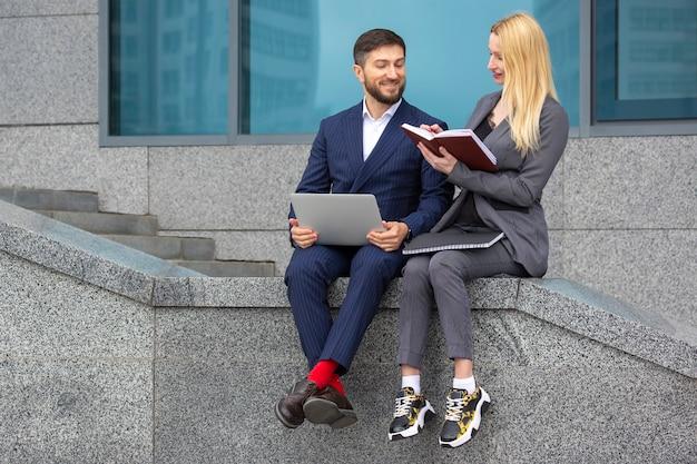 Des hommes d'affaires prospères, hommes et femmes, sont assis dans les escaliers d'un immeuble commercial avec des documents et un ordinateur portable dans les mains pour discuter de projets d'entreprise