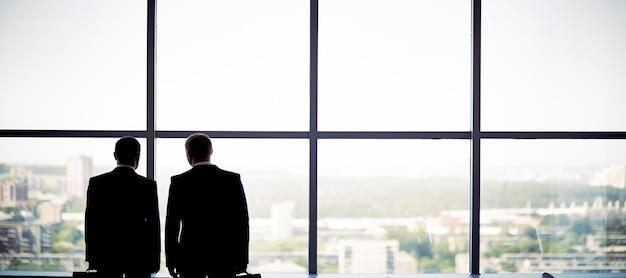 Les hommes d'affaires en regardant à travers la fenêtre