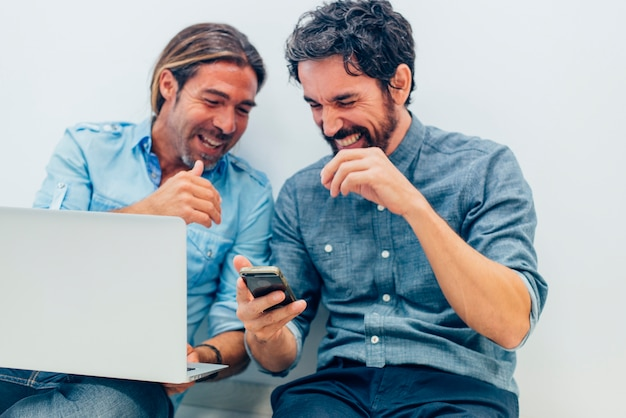Les hommes d'affaires rire tout en regardant le mobile