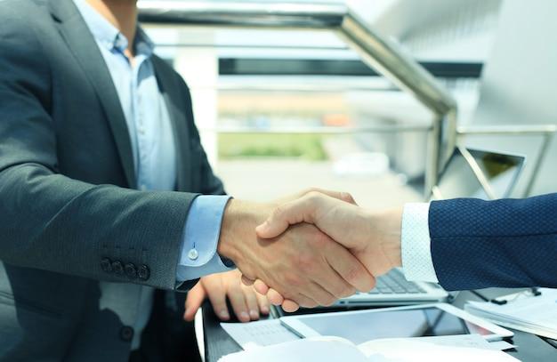 Des hommes d'affaires se serrant la main, terminant une réunion.