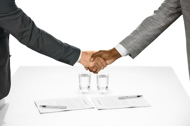 Les hommes d'affaires se serrent la main. le contrat est signé. bienvenue dans l'équipe. démarrage d'un partenariat.