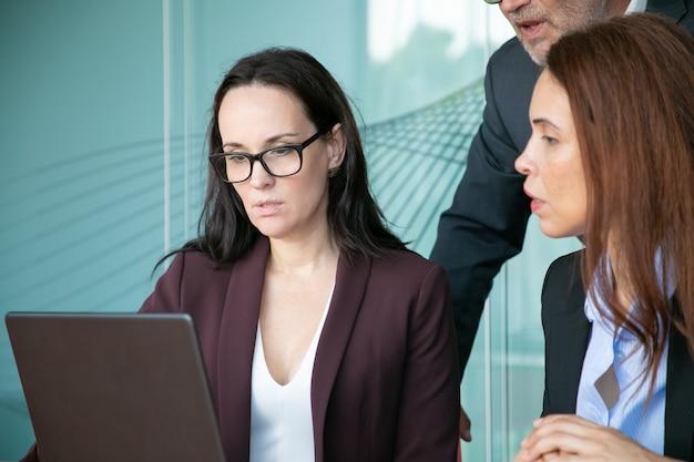 Hommes d'affaires sérieux ciblés assis et debout à un ordinateur portable ouvert, regardant l'écran.