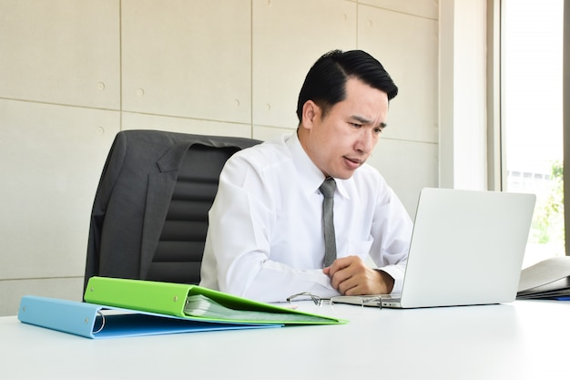 Les hommes d'affaires sont stressés par le dur labeur assis sur l'ordinateur avec le téléphone.