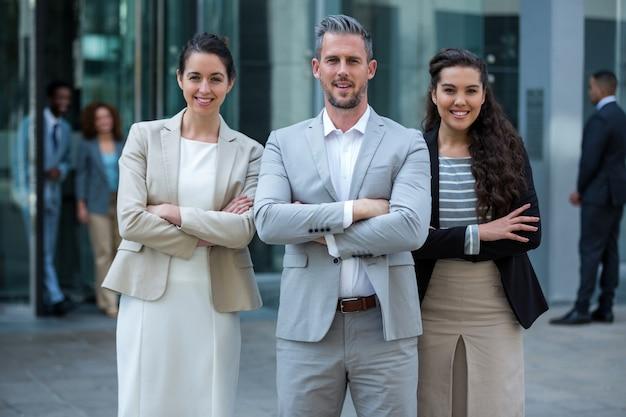 Hommes d'affaires souriants debout avec les bras croisés à l'immeuble de bureaux
