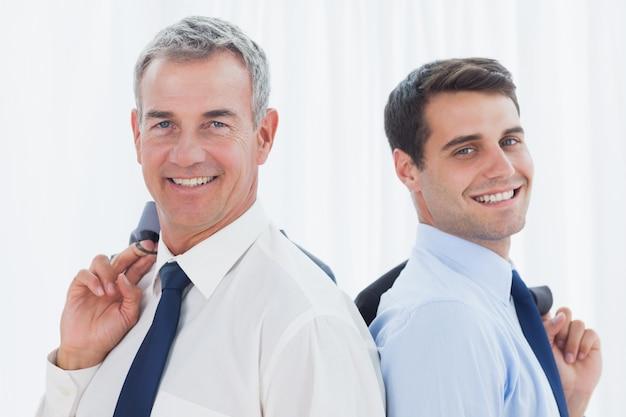 Hommes d'affaires souriants posant dos à dos ensemble tout en tenant leur veste