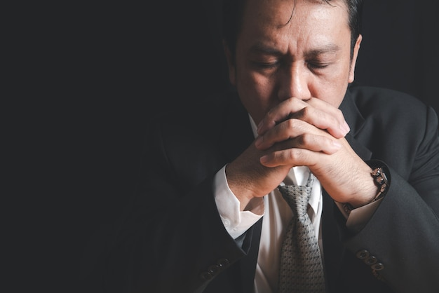 Les hommes d'affaires stressés mettent leurs mains ensemble tout en examinant des histoires sur les performances de l'entreprise, le concept de problèmes de stress au travail.