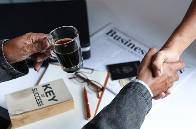 Les hommes d'affaires tenant une tasse de café sont serrer la main.